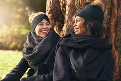 Close-up of two smiling young women leaning on tree trunk in autumnal park Stock Images