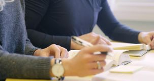 Close-up of two students studying at school library. Close-up of two collaborating students who reading and taking notes. Man and woman studying at a college or stock footage