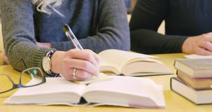 Close-up of two students team working in school library. Close-up of two collaborating students who reading and taking notes. Man and woman team up and studying stock footage
