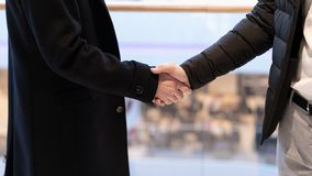 Close up of two successful businessmen greeting each other against the background of look on the city. Business handshake in the stock photo