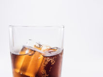Close up two of thirds soft drink. Is cool and ice cubes in glass on white background royalty free stock photo