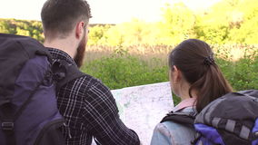 Close-up of two tourists with backpacks and map. Close-up of two tourists a man and a woman with backpacks reading a map and look for the road. View from the stock video footage