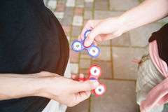 Close-up Two tweens spinners on the street against each other stock photography