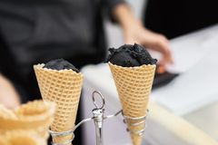 Close-up of two waffle cones, horns with balls of trendy black ice cream and hand of the seller. Delicious cooling. Portion for fun. Selective focus. Real scene stock photo