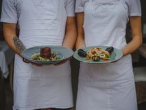 Couple of waiters holding plates. Waiter and waitress serving food on a blurred background. Classic restaurant concept. Stock Photography