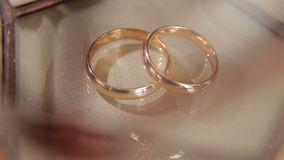 Close-up of two wedding rings on beige background. Close-up of two wedding rings on a beige background with patches of light stock video footage
