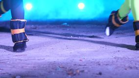 Close-up of two women legs with weightings on, doing fitness exercises , At night, in light smoke, fog, in light of. Multicolored searchlights, in an old stock footage