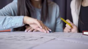 Close-up of two women with pen discussing an interior drawing on paper. stock video footage