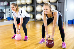 Close-up of two women training with kettlebells at gym Royalty Free Stock Photos