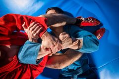 Man wrestler makes submission wrestling. Close-up two wrestlers of grappling and jiu jitsu in a blue and red kimono makes armlock. Wrestler submission wrestling stock images