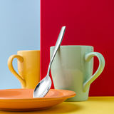 Close up of two yellow and blue cups on a yellow table and blue and red background with an empty space. Empty cups for coffee, colorful option Royalty Free Stock Photo