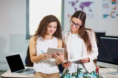 Two young business girls are examining documents and a tablet stock photo