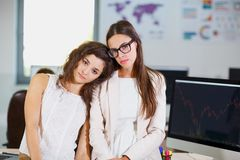 Two young business girls in white blouses at the office are tired. Close-up of two young business girls in white blouses who are tired of work Royalty Free Stock Images