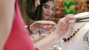 Close-up of two young shopping women reflected in the mirror. Two young shopping women looking at jewelry. They are reflected in the mirror. Close-up shot stock video footage