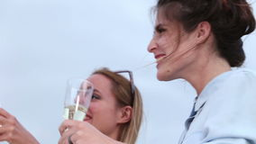 Close up of two young women drinking champagne. Close up of two beautiful young women drinking champagne and smiling stock video footage