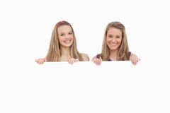 Close-up of two young women holding a blank sign Royalty Free Stock Images
