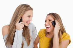 Close-up of two young women laughing on the phone Royalty Free Stock Image