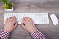 Close-up of typing male hands on keyboard. From above Royalty Free Stock Photography