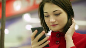Close-up typing woman on a smartphone device. In public place stock footage