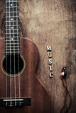 Close up of ukulele and earphone on old wood background Royalty Free Stock Photos