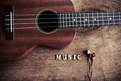 Close up of ukulele and earphone on old wood background Stock Photos
