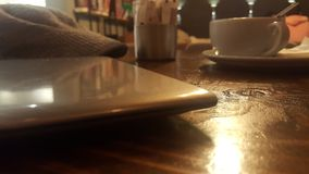Close up of an ultrabook, coffee cup and cap on wooden desk in a cafeteria. Creative class and knowledge worker concept. More and more people work in ambivalent stock images