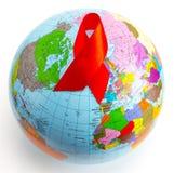 Close up um globo do mundo com uma fita vermelha para a luta contra o AI fotos de stock