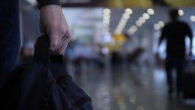 Close-up Um homem leva um saco em sua mão Aeroporto ou estação de caminhos de ferro 4K mo lento vídeos de arquivo