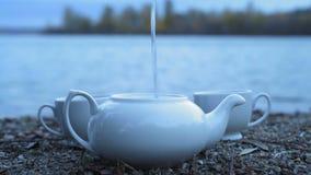 Close-up, um jato da água a ferver que derrama em uma posição branca do bule da porcelana em um banco de rio rochoso video estoque