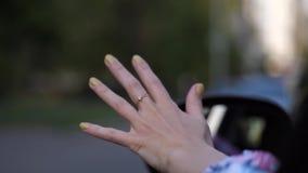 Close-up Um motorista fêmea durante uma viagem colou-a para distribuir e faz ondas através do ar 4K mo lento filme