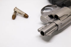 Close-up um revólver com as balas isoladas no fundo branco Foto de Stock Royalty Free