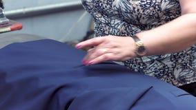 Close-up: Uma mulher da costureira cozinha um revestimento usando um ferro antiquado A mão de uma mulher guarda o ferro e alisa video estoque