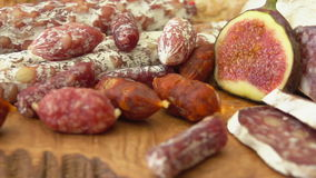Close up uncooked jerked sausages and figs. Close-up camera movement near uncooked jerked sausages and figs on a wooden board stock video