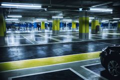 Close up on underground parking with empty slots and car Stock Photography