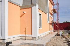 Close up on unfinished house paining walls and concrete path for foundation waterproofing. Foundation construction stock photo