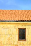 Close up unfinished roof. Roof house with tiled roof on blue sky. marble tile on the wall in a new window. Unfinished roof. Stock Images