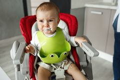 Close up of unhappy little one years son in green bib screaming and crying in chair for babies after mom made him eat. Porridge Stock Photo