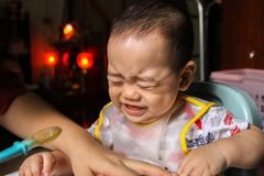 Close up of unhappy little seven months old son in see through plastic bib screaming and crying in chair for babies after mom made. Him eat avocado and banana Stock Photo