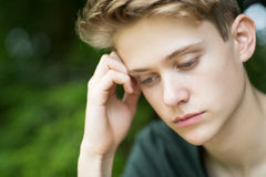 Close Up Of Unhappy Teenage Boy Sitting Outdoors stock images
