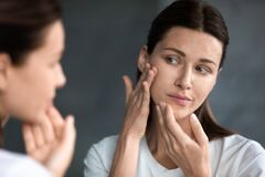 Free Close Up Unhappy Woman Looking At Acne Spots In Mirror Royalty Free Stock Image - 169763696