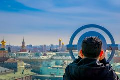 Close up of unidentified man using a metallic structure of coin operated binocular enjoying the city behind of Moscow. Business centers and skyscrapers and the Royalty Free Stock Photography