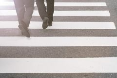 Close-up on unidentified people legs crossing street. Close-up onbusinessman legs crossing street Royalty Free Stock Image
