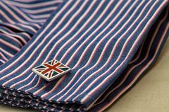 Close up of Union Jack flag design cufflink and fashionable work shirt. Close up of Union Jack flag design cufflink and fashionable stripy work shirt stock photography