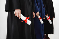 Close up of university students graduates in mantles holding diplomas over white background. Stock Photos