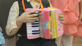 Boy playing on toy accordion stock video