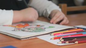 Child draws the pictures using color pencils stock video