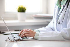 Close up of  unknown female doctor sitting  at the table near the window in hospital Royalty Free Stock Photography