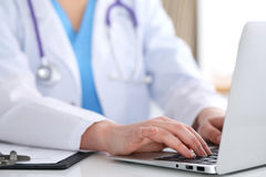 Close up of unknown female doctor typing on laptop computer while sitting  at the table Stock Photography