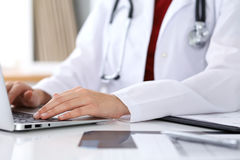 Close up of unknown female doctor typing on laptop computer while sitting  at the table Stock Image