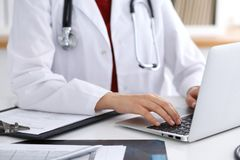 Close up of unknown female doctor typing on laptop computer while sitting  at the table Stock Photos